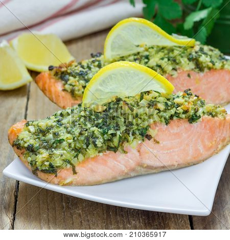 Baked salmon with macadamia cilantro crust on a white plate square format