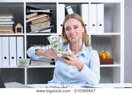 Beautiful businesswoman portrait. Scattering money notes dollars in fashion vows style mulatto curly hair with white locks eye view of the camera