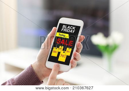Female hands holding phone with sale black Friday screen in room home