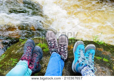 Traveler hiking boots near river on nature background. Trekking shoes of family relaxing after hiking. Travel healthy active lifestyle. Outdoor freedom. Feet selfie.