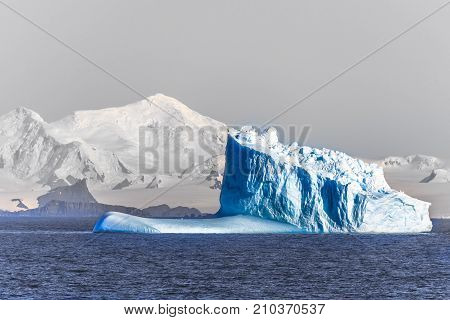 Three huge blue icebergs drifting across the sea at Lemaire Channel Antarctica