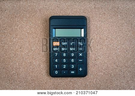 One black classic calculator in the center of cork floor background with copy space around calculator. Black calculator for background.
