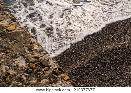 Textures of pebble beach sea foam and concrete slab photographed according the rule of triangle
