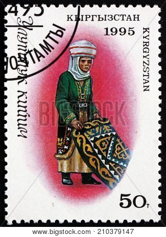 KYRGYZSTAN - CIRCA 1995: a stamp printed in the Kyrgyzstan shows Woman in Traditional Kyrgyz Costume with Carpet circa 1995