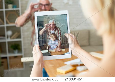 Portrait of little boy with his grandpa posing for photo taken via digital tablet, image on screen