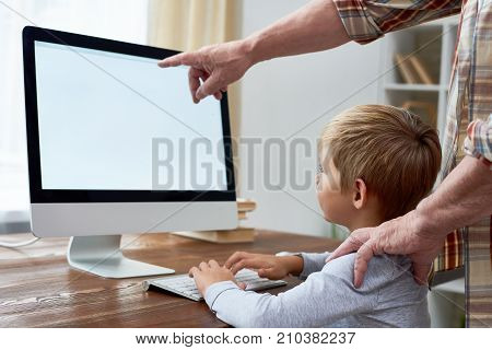 Portrait of little boy learning to use modern pc sitting at desk and doing homework with grandpa explaining him something pointing at blank white screen