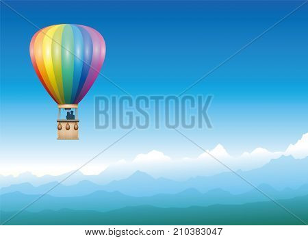 Captive balloon peacefully drifting through a misty blue mountain landscape - rainbow colored flying vehicle with two people enjoying their freedom, the great view and the mystical panorama.