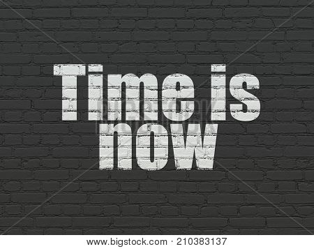 Time concept: Painted white text Time is Now on Black Brick wall background
