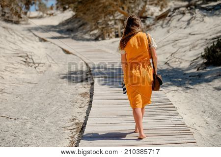 Young beautiful girl in a dress barefoot walking on a wooden walkway. View from the back