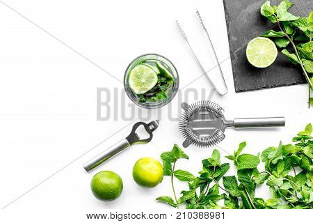 Make mojito cocktail with lime and peppermint. White background top view.