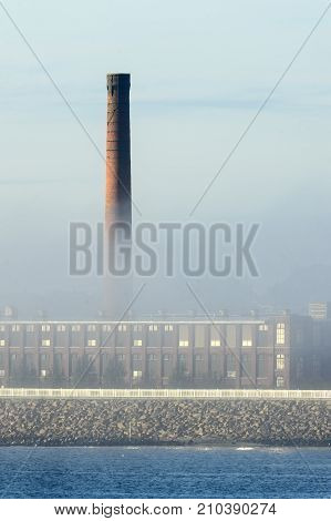 Smokestack at waterfront factory rising above morning fog