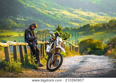 on a off road motocross track a biker rest at the sunset on a wooden fence in the Colli Euganei Italy 22 Apr 2017