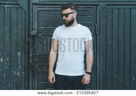 Summer day. Front view. Young bearded hipster man dressed in white t-shirt and sunglasses is stands against dark wood wall. Mock up. Space for logo, text, image. Advertising.