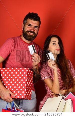 Couple In Love Holds Shopping Bags On Red Background