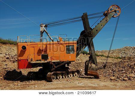 Retro excavator in open pit