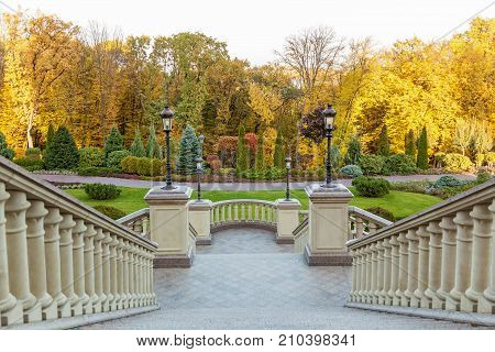 stone staircase in the Mezhyhirya Park, staircase with lanterns against the background of autumn trees