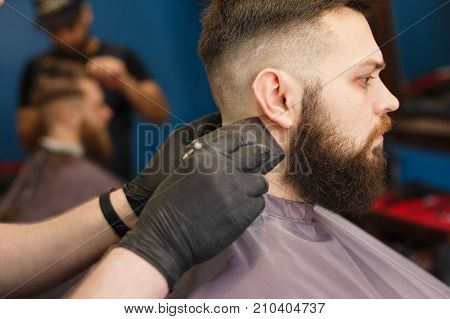 Barber styling beard with trimmer at barbershop, closeup of client's head. Barbershop for men