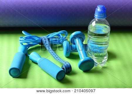 Skipping Rope, Cyan Dumbbells And Tape Near Water Bottle