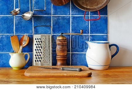 Kitchen interior still life. Vintage utensils ceramic pitchers, cutting board, knife, wooden spoon, pepper and metallic grater. Blue tiled wall background photo.