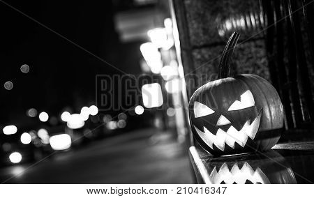 BLACK WHITE concept of Halloween. Pumpkin with a face stands on the street and decorates the street scaring passers-by people.