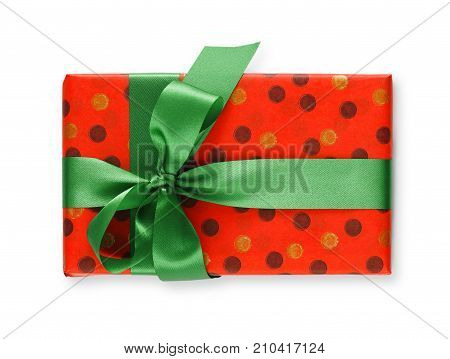 Gift box wrapped in dotted red paper and green satin ribbon, isolated on white background. Modern present for any holiday, christmas, valentine or birthday