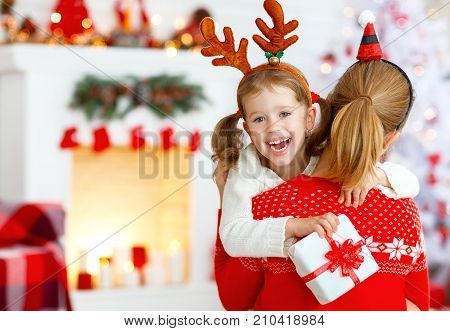 happy family mother and daughter giving christmas gift and embracing