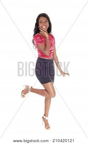 33f912e37d A young beautiful slim African woman standing in a pink blouse and black skirt  lifting one