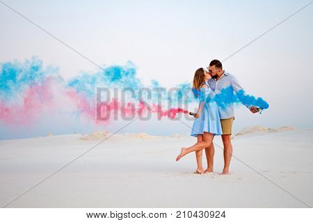young couple kissing and holding colored smoke in hands romantic couple with blue color and red color smoke bomb on beach