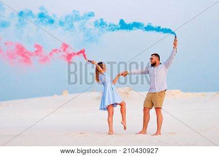 young couple standing on a sand and holding smoke bomb and looking at each other romantic couple with blue color and red color smoke bomb on beach