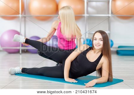 Attractive young fitness woman doing leg raises exercising with her personal trainer at the gym weight loss slimming shaping aerobics sport sportspeople lifestyle workout concept