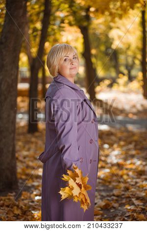 Full length of a beautiful, smiling and adult woman in purple coat with blonde hair and with a bouquet of maple yellow leaves on a blurred autumn park background.
