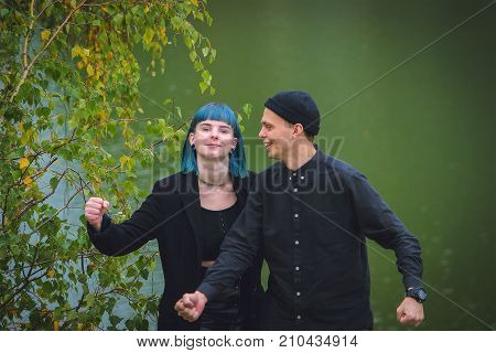 Informal Girl With Blue Hair And A Man With Pale Skin In Black Clothes At The Street Walking