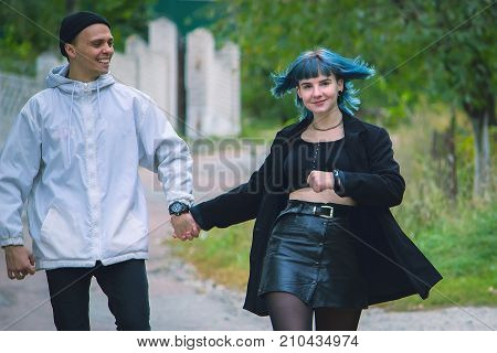 Informal Girl With Blue Hair And A Man With Pale Skin At The Street Walking