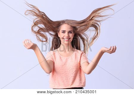 Funny young lady in a pink Tshirt smiling in studio. Cutie girl tosses long hair posing on camera on a gray background. Close-up of girl.