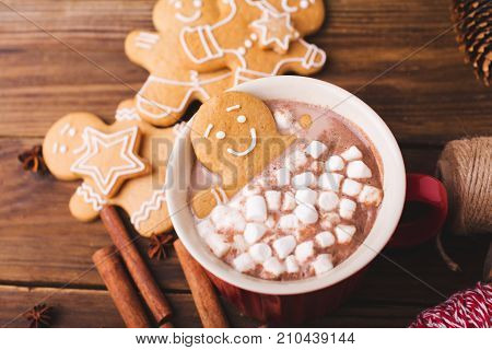 Gingerbread man bathes in a cup of hot chocolate or cocoa with marshmallow. Gingerbread Man in red cup