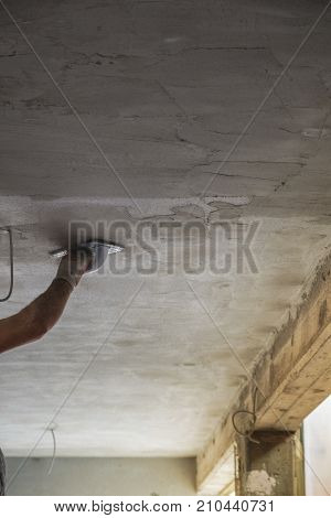 Construction worker scraping the cement plaster surface of the ceiling