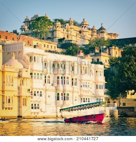Water view of City Palace in Udaipur City Of Lakes in Rajastan, India. Red boat on Pichola Lake in Udaipur