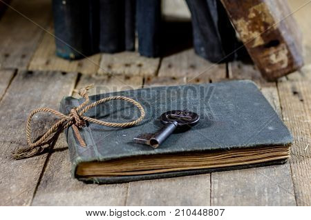 Very Old Book And Key On An Old Wooden Table. Old Room, Wooden Table And Book With Key.