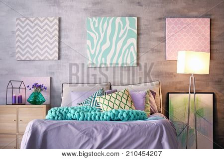 Lilac accent in modern interior. Comfortable bed with pillows and plaid in room