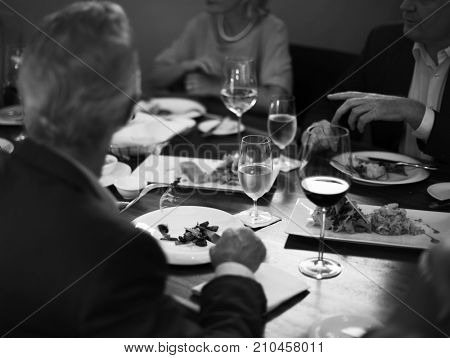 Group of people having dinner in the restaurant together grayscale