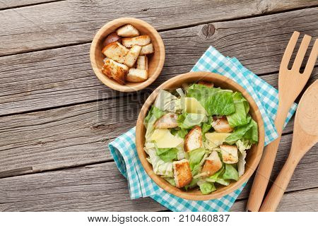 Fresh healthy caesar salad on wooden table. Top view with copy space