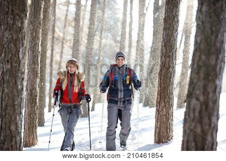 Young couple of hikers on snowy winter hiking on mountain