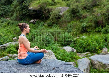 Woman in Hatha yoga asana Padmasana outdoors