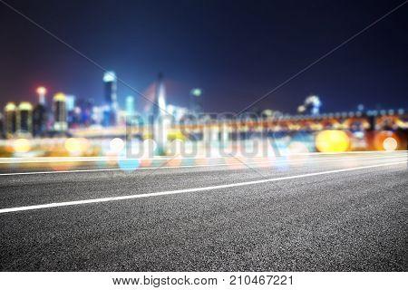 empty asphalt road and blur view of modern suspension bridge in chongqing at night
