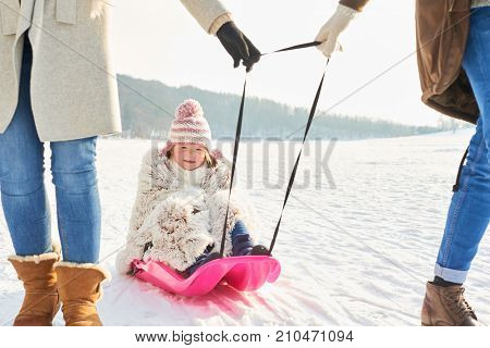 Parents with child sledging in winter while taking a walk in the snow