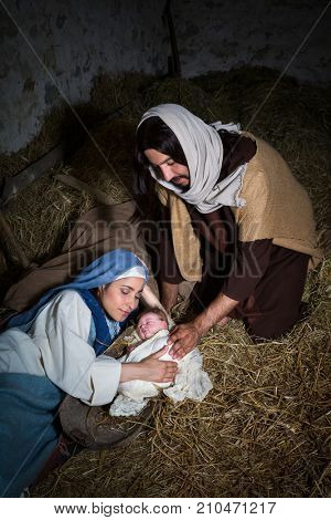 Live Christmas nativity scene in an old barn, reenactment play with authentic costumes. The baby is a property released doll.