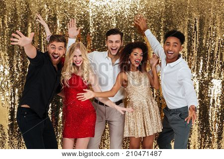 Group of happy friends celebrating new year and having fun together isolated over shiny golden background