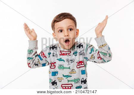 Portrait of a shocked little kid standing and shrugging shoulders isolated over white background