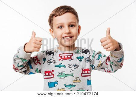Portrait of a smiling little kid standing and showing thumbs up with two hands isolated over white background