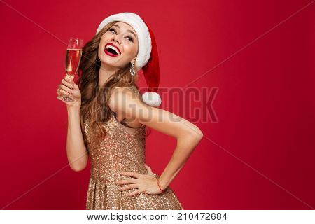 Portrait of a beautiful smiling woman in christmas hat and dress holding champagne glass while standing and looking up isolated over red background